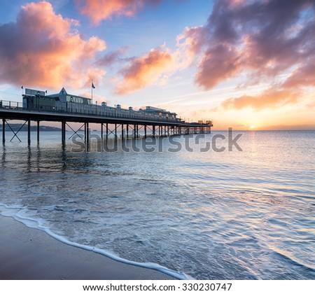 Sunrise over the pier at Paignton on the Devon Coast - stock photo