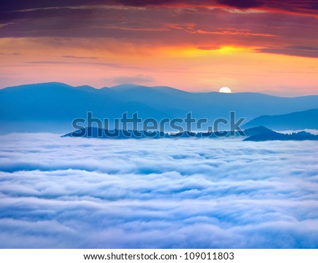 Sunrise over the sea of fog in the mountains at the summer - stock photo