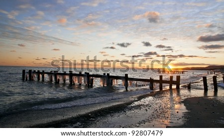 sunrise over winter lake with old dock pilings - stock photo