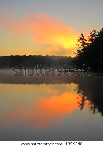 Sunrise reflected off of a misty calm lake in Wisconsin - stock photo
