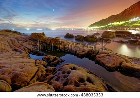 Sunrise scenery at the rocky coast in northern Taiwan, with view of puddles on the rocks at a beautiful beach, lights of the coastal highway and fishing boats on the distant horizon under dramatic sky - stock photo