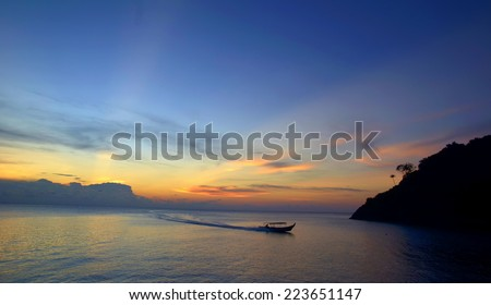 Sunrise Seascape with Fisherman Boat on the Sea (Soft focus, shallow DOF, slight motion blur) - stock photo