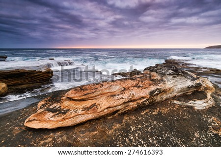 Sunrise seascape with orange rocks and ocean pools and sea shells with cloudy stormy sky and distant cliffs - stock photo