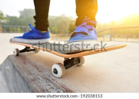 sunrise skateboarding woman legs - stock photo