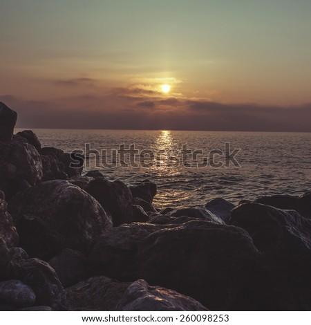 sunrise sun sea pebble stones - stock photo