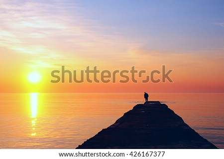 sunrise, sunset, lonely silhouette of a man standing at the end of Fisherman's longest pier, a pier with a fishing rod in hand. Beautiful golden sun shines all around the golden light.  - stock photo