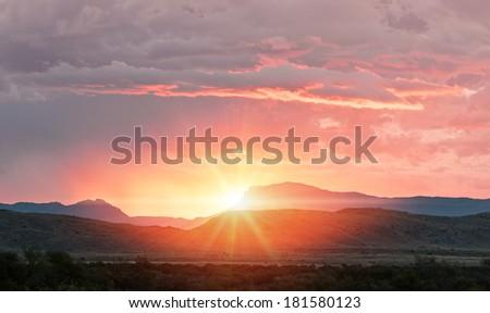 sunrise sunset over the distant mountain horizon - stock photo