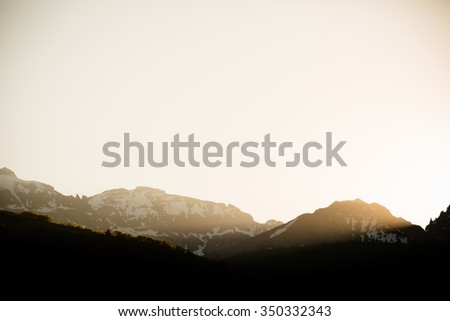 Sunrise - This is a beautiful image of the warm sun streaming through the mountain peaks in Telluride, Colorado. Shot with a warm color tone.  - stock photo