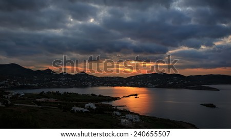 Sunrise through clouds at Finikas bay, in Syros island, Greece  - stock photo