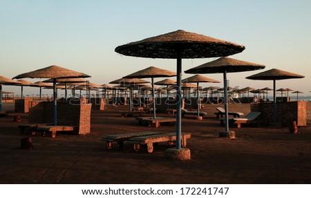 Sunrise under Egyptian parasols on the beach - stock photo