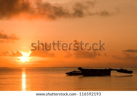 Sunrise with an African boat (dhow) in the foreground - stock photo