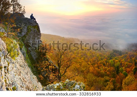 Sunrise with inversion above the deep autumn valley of mountains with small man on the top, who is watching this beautiful scenery - stock photo