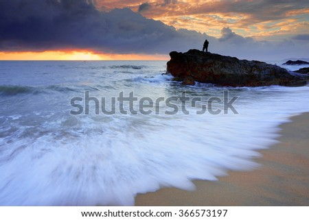 Sunrise with wave and Silhouette of Photographer at Kemasek Beach taken with Slow Shutter. Soft Focus Motion Blur due to Slow Shutter Speed. Copy Space Area - stock photo