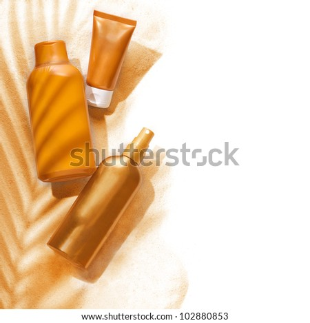 Sunscreen containers in a tropic ambiance on white background. - stock photo