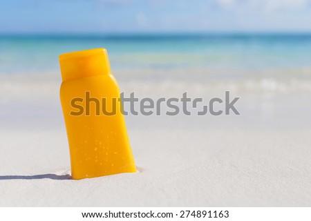 Sunscreen cream bottle on the beach - stock photo