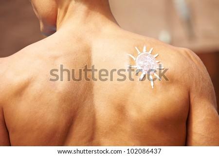 Sunscreen in sun shape on a male back - stock photo