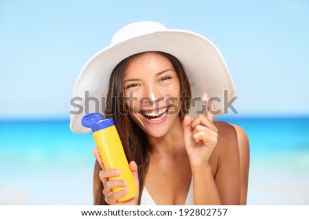 Sunscreen woman applying suntan lotion showing bottle. Beautiful smiling happy asian woman with suntan cream in plastic container lying on beach during summer travel vacation. Multiracial female model - stock photo