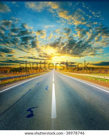 Sunset above asphalt road - stock photo