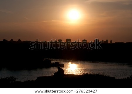 Sunset above the city and the river - stock photo