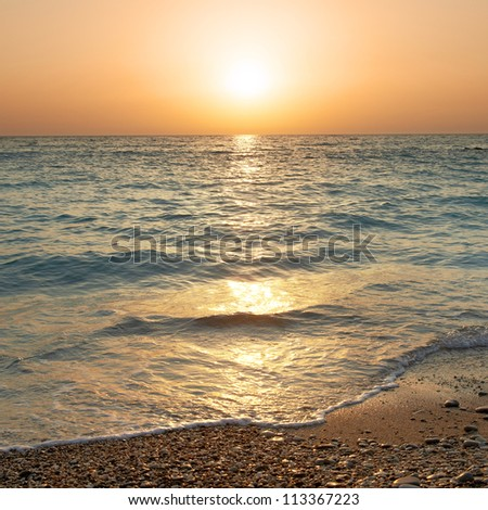 Sunset above the sea. Big sun and waves at beach - stock photo