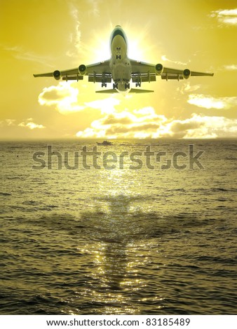 Sunset and airplane fly over ocean - stock photo