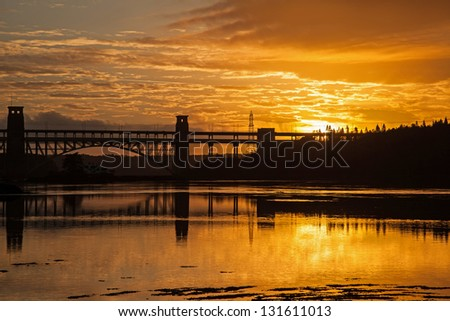 Sunset and Brittania Bridge from Church Island Menai Bridge Isle Anglesey North Wales - stock photo