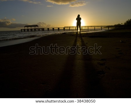 Sunset and cameraman on the beach at the Kauai, Hawaii - stock photo