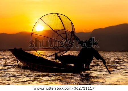 Sunset and fisherman on Inle Lake. Inle Lake with its leg-rowing Intha people is a major tourist destination in Burma. - stock photo