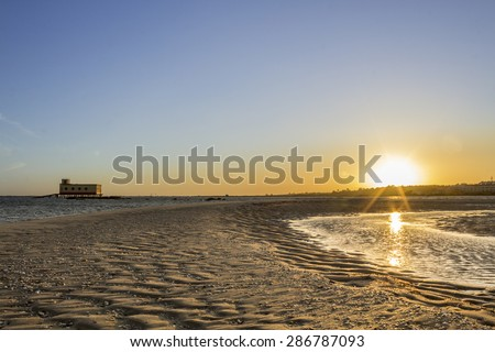 Sunset and historic life-guard building in the foreground, at Fuseta fishing town, Ria Formosa conservation park, Algarve. Portugal - stock photo