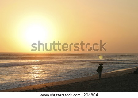 Sunset and seller at Kuta Beach Bali - stock photo