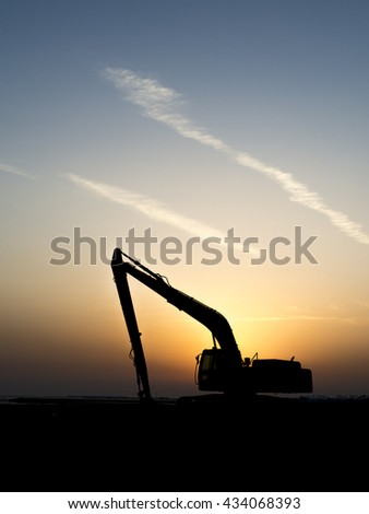 Sunset and silhouette of excavator on the reclamation land.   - stock photo