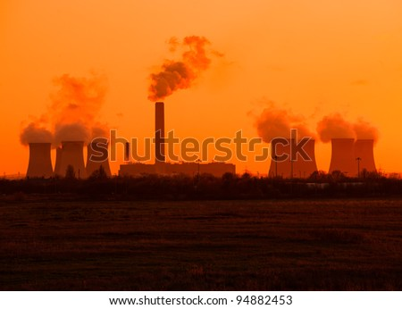 Sunset and smoke from a coal burning power station - stock photo