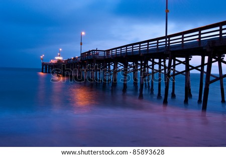 Sunset as seen from shore, looking out directly at Balboa Pier, Newport Beach, California. - stock photo