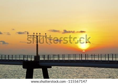 Sunset at airport runway lights in Hong Kong - stock photo