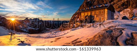 Sunset at alpine hut in winter - stock photo