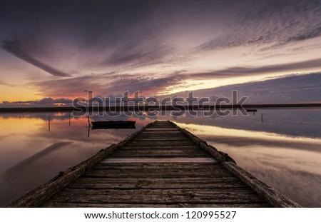 Sunset at an old wooden jetty on the Fleet lagoon near Weymouth in Dorset. - stock photo
