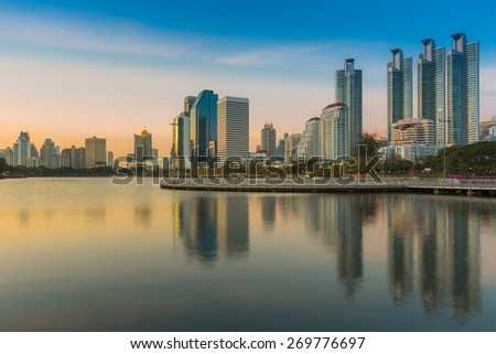 Sunset at Bangkok city downtown twilight with reflection of skyline,Benjakitti Park, Thailand - stock photo