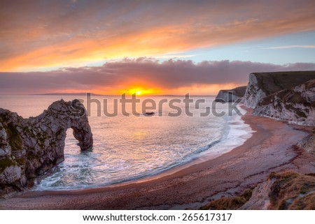 Sunset at Durdle Door natural limestone arch on the Jurassic Coast near Lulworth in Dorset England UK Europe - stock photo