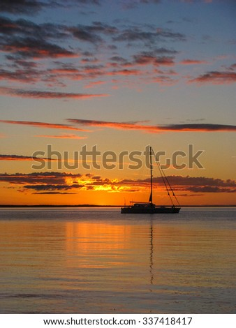 Sunset at fraser Island with boat on the ocean - stock photo