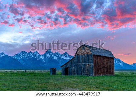 Sunset at Grand Teton - A sunset view of an abandoned old barn in historic Mormon Row area, in southeast part of Grand Teton National Park, with Teton Range rising high in the background, Wyoming, USA - stock photo