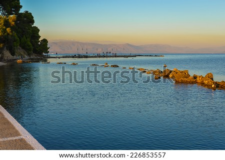 Sunset at Kanoni beach in Corfu Town at Corfu Island Greece with Greek mainland mountains in the background - stock photo