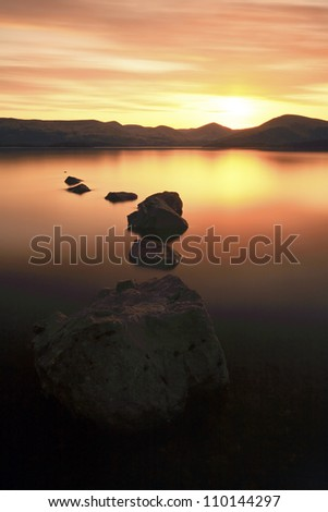Sunset at Loch Lomond with rocks leading in to the water - stock photo