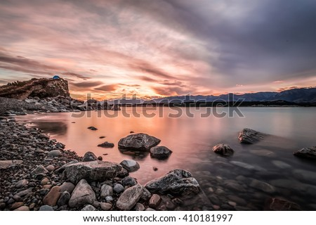 Sunset at Mount Cook National Park alongside Lake Pukaki with snow capped Southern Alps basking in the late winter afternoon's golden light. The setting sun cast vivid pastel  hues on the sky. - stock photo