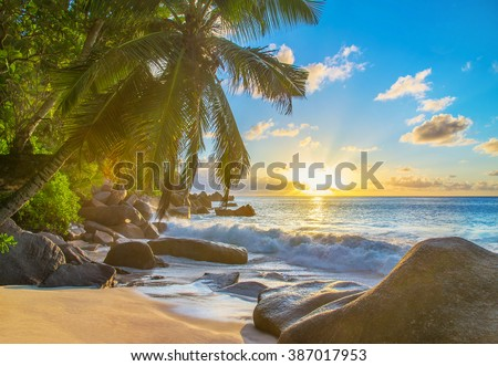 Sunset at picturesque sandy tropical palm beach with large granitic boulders, Anse Georgette, Praslin island, Seychelles, nature background - stock photo