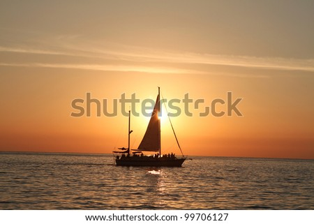 Sunset at sea with a sailboat. - stock photo