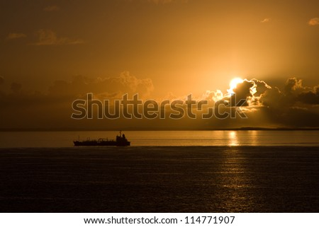 Sunset at sea with cargo ships in the background - stock photo
