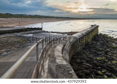 Sunset at Seaton Sluice Harbour, Northumberland, England, UK. View looking at harbour walls and seaside. - stock photo