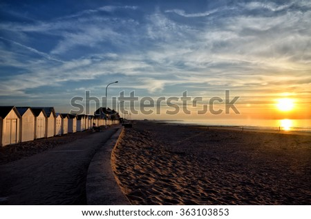 Sunset at the beach in Normandy with bathing hut - stock photo