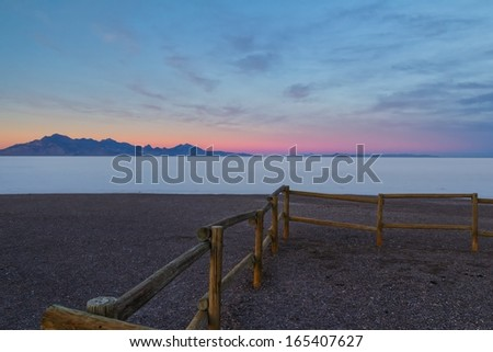 Sunset at the Bonneville salt flats in Utah USA/Fence By the Salt Flats - stock photo
