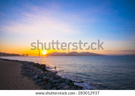 Sunset at the Famous Golden Gate Bridge, San Francisco, California, USA.  View from Crissy Field.  Rocks on the beach sands. - stock photo